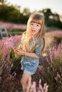 Amusing girl sniffing flowers in a lavender field Royalty Free Stock Photo