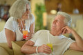 Amusing old couple on vacation drinking cocktail Stock Photos