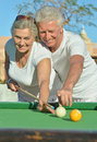 Amusing old couple on vacation playing billiards Royalty Free Stock Photo
