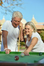 Amusing old couple on vacation playing billiards Stock Image