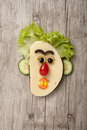 Amusing sandwich face made on wooden background Stock Image