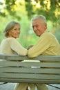 Amusing senior couple sitting on bench in park Stock Photos