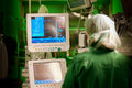 Anaesthesiolog female at monitors in surgery room with information on them operation with green lights on back view Royalty Free Stock Images
