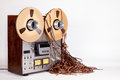 Analog open reel tape deck recorder with messy tape tangled on white Royalty Free Stock Photos
