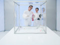 Analyzing raw meat in sterile chamber two scientists the lab a men and a woman a chunk of a Stock Image