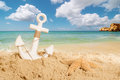 Anchor on the beach with starfish a sandy summer holiday concept Stock Image
