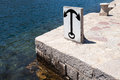 Anchor sign on stone embankment in kotor bay montenegro Royalty Free Stock Photography