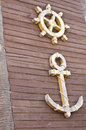 Anchor steering wheel symbol old wooden wall Royalty Free Stock Photo