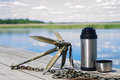 Anchor with a thermos of tea on a background of nature are at the pier Royalty Free Stock Photo