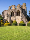 Ancient abbey ruins the of th century wenlock priory in summer sunshine with topiary and a lawn in front much wenlock shropshire Stock Photo