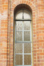 Ancient arched window with stained glass in brick wall Royalty Free Stock Photo
