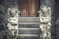 Ancient Asian demons deities at the enter to the old temple with old wooden door and stone steps in vintage style Royalty Free Stock Photo