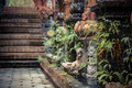 Ancient Asian style garden alley with old column overgrown with tropical plants and blurred background