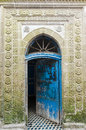 Ancient blue door with carved stone decoration entrance and intersting floor tiles in the old town of essaouira in morocco Royalty Free Stock Image
