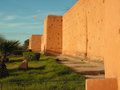 Ancient fortifications thick wall surrounding marrakech s medina adjoined by lawns and path Stock Photography