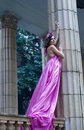 Ancient goddess description beautiful young woman model wearing pink violet silk tunic dress posing as an near columns Royalty Free Stock Photo
