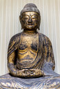 Ancient gold bronze buddha statue in traditional sitting pose Stock Photo