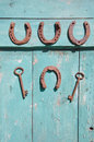 Ancient horseshoe and rusty key on wooden old door Royalty Free Stock Photo