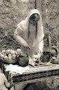 Ancient kitchen young lady preparing food in on traditional way woman in white coat cooking on old fashioned way Stock Image