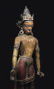 Ancient nepal statue isolated of the bodhisattva or buddhist teacher carved from wood and painted from on black Stock Images