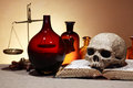 Ancient pharmaceutics human skull on old books near weight scales and glass flasks Stock Photography