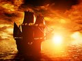 Ancient pirate ship sailing on the ocean at sunset Royalty Free Stock Photo