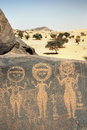 Ancient rock art in Sahara depicting three figures Royalty Free Stock Images