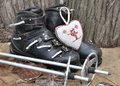 Ancient ski boots old in a rustic setting with a heart shaped cushion Royalty Free Stock Photo
