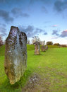 Ancient standing stones view of at avebury england with dusk sky behind Stock Photo