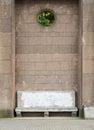 Ancient stone bench near the big brick wall Royalty Free Stock Photo