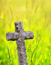 Ancient stone cross with green summer field in background Royalty Free Stock Images