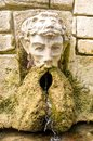 Ancient stone fountain. Fountain with head of man
