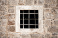 Ancient stone prison wall with window metal bars Royalty Free Stock Photography