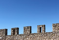Ancient stone wall with battlements perspective a foreshortened view of an against a bright blue sky from the medieval castle of Royalty Free Stock Photos