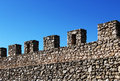 Ancient stone wall with battlements perspective a foreshortened view of an against a bright blue sky from the medieval castle of Stock Photos
