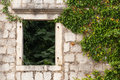 Ancient stone wall with empty window abandoned house fragment and plants perast town montenegro Stock Photo
