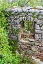 An ancient stone wall of a ruined house with a window among the grass. Old house, ruins, background Royalty Free Stock Photo