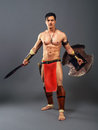 Ancient warrior half naked man in the image of on a gray background Stock Photos