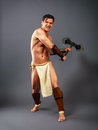 Ancient warrior kick axe half naked man in the image of strikes with melee weapons on a neutral grey background Stock Photo