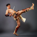 Ancient warrior kick half naked man in the image of an strikes his foot on a neutral grey background Stock Photo