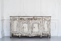 Ancient white commode bureau with paint peeled off on luxury wall design bas-relief stucco mouldings roccoco elements