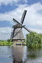 Ancient wind mill reflected in a blue canal on a summer day Royalty Free Stock Photo