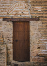 Ancient wood door in brick wall at spanish historic palace under arch on stone and grenada spain Stock Images