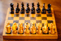 Ancient wooden chess standing on chessboard Royalty Free Stock Photo
