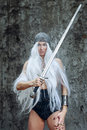 Androgyne girl with long white hair in chain mail and sword Royalty Free Stock Photography