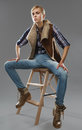 Androgynous girl sits on a chair jeans and jacket Royalty Free Stock Photos
