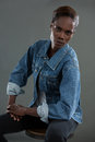 Androgynous man in denim jacket posing against grey background Royalty Free Stock Photo
