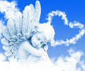 Angel dreams before heart from clouds Stock Images