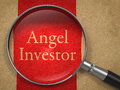 Angel investor through a magnifying glass on old paper background Stock Photo