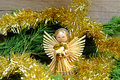 Angel made of straw with a star on his forehead for him christmas chain in gold color old wooden table green needles Royalty Free Stock Photography